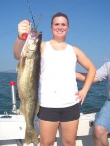 a young woman holding a trophy walleye taken on bring it on lake erie charters out of ashtabula ohio lake erie